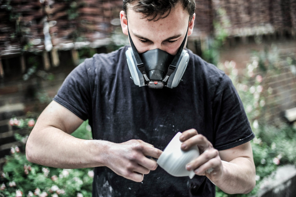 Dominic wearing a ceramic grade dust mask to dry sand a piece in a well-ventilated area.