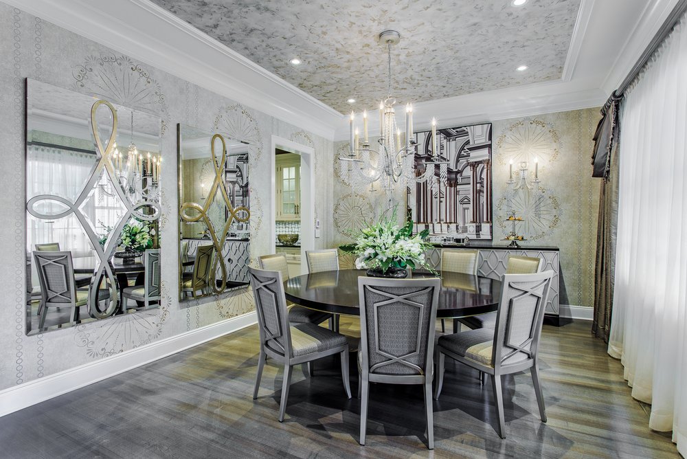 The dining room opens to the foyer and kitchen. A custom-made 80-inch round dining table with chairs in platinum finish. The attractive detail on the back of the chairs adds grace and complements the delicate crystal ribbon feature of the chandelier. Two large scale mirrors enhance the wallcovering and faux painted ceiling.