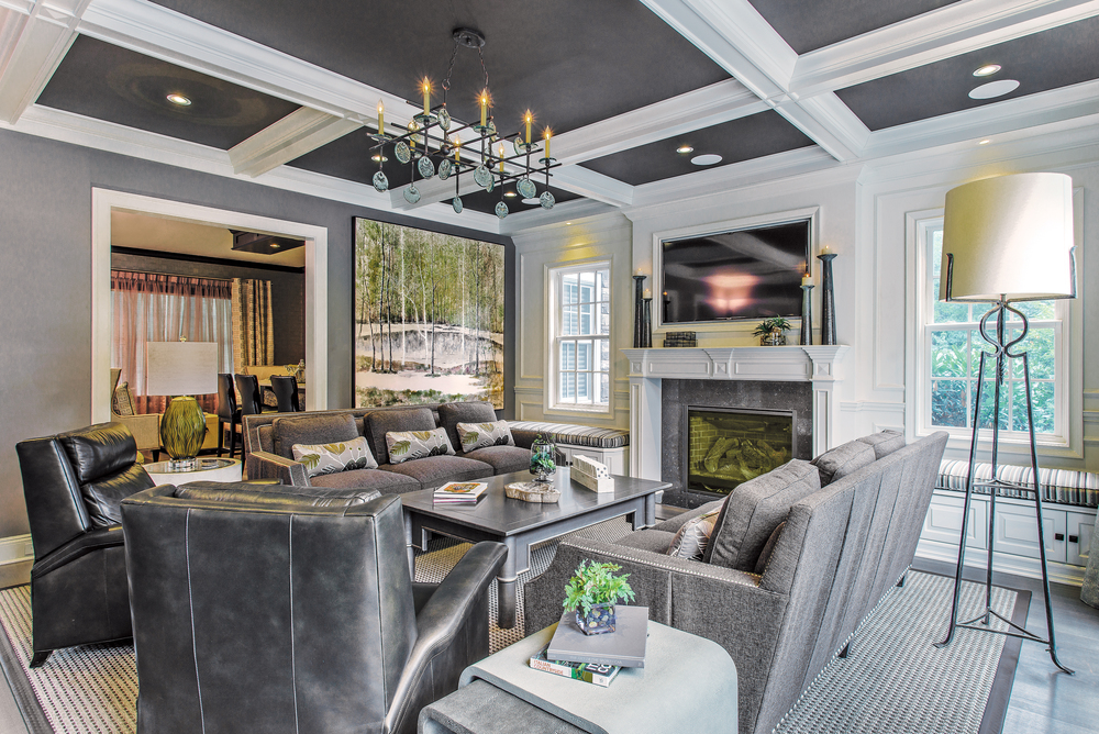 ­Family room off the kitchen with dark gray coffered ceiling. An iron and hand-blown glass light fixture meshes with the continuity of the ceiling. The fireplace with the opposing sofas and leather recliners is welcoming.