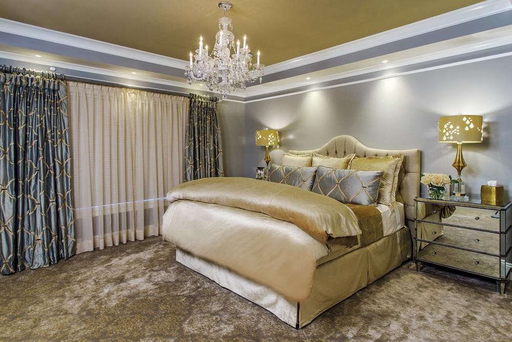 A shaped tufted headboard in the master bedroom is covered in a raw silk. The mirrored nightstands, gold and crystal lamps with their laser cut and crystal shades add a touch of graceful charm.This room blends romance and elegance with a soft palette of gray and gold.