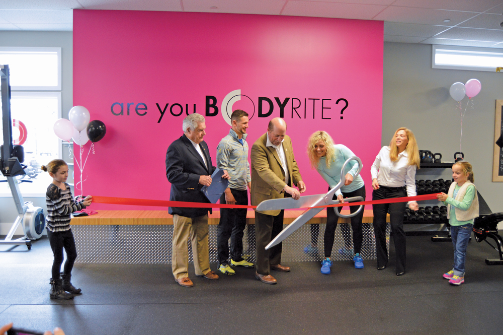Paige ceremoniously cuts the ribbon to officially open the BodyRite studio