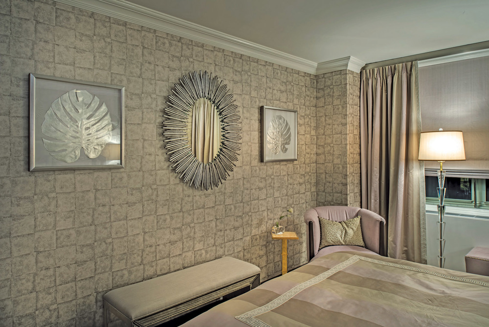 The mirror is a sunburst in silver metal flanked by silver leaf motif wall décor.