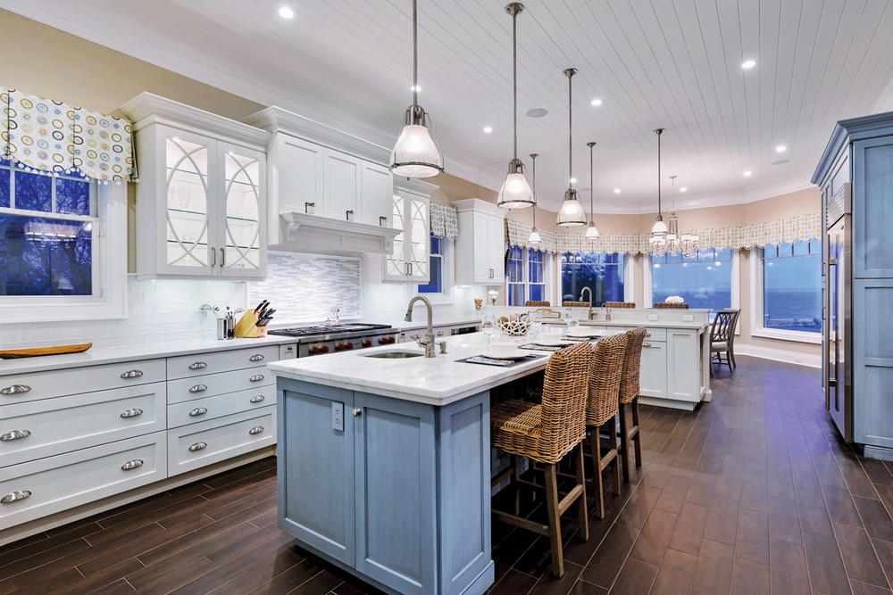 Crisp, white cabinetry enhances the cool blue center island with marble countertops.