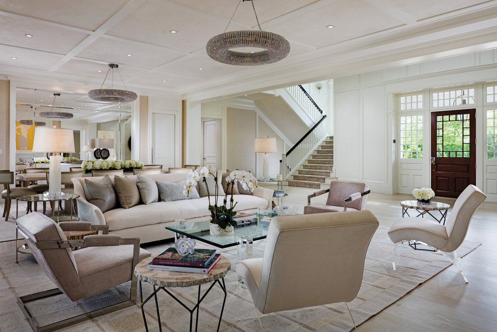 "The living room offers a coffered ceiling and gas ""Lido White"" marble fireplace. The adjacent dining room features a coffered ceiling and mirrored walls."