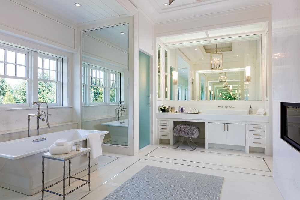 In the master bath, a steam shower, Toto water closet, decorative tub, linear fireplace and two separate vanities detail this marble oasis.