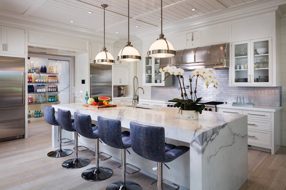 "The paneled kitchen is a signature Kean delight, trimmed in high gloss cabinetry and a fabulous ""Carrera"" porcelain center island."