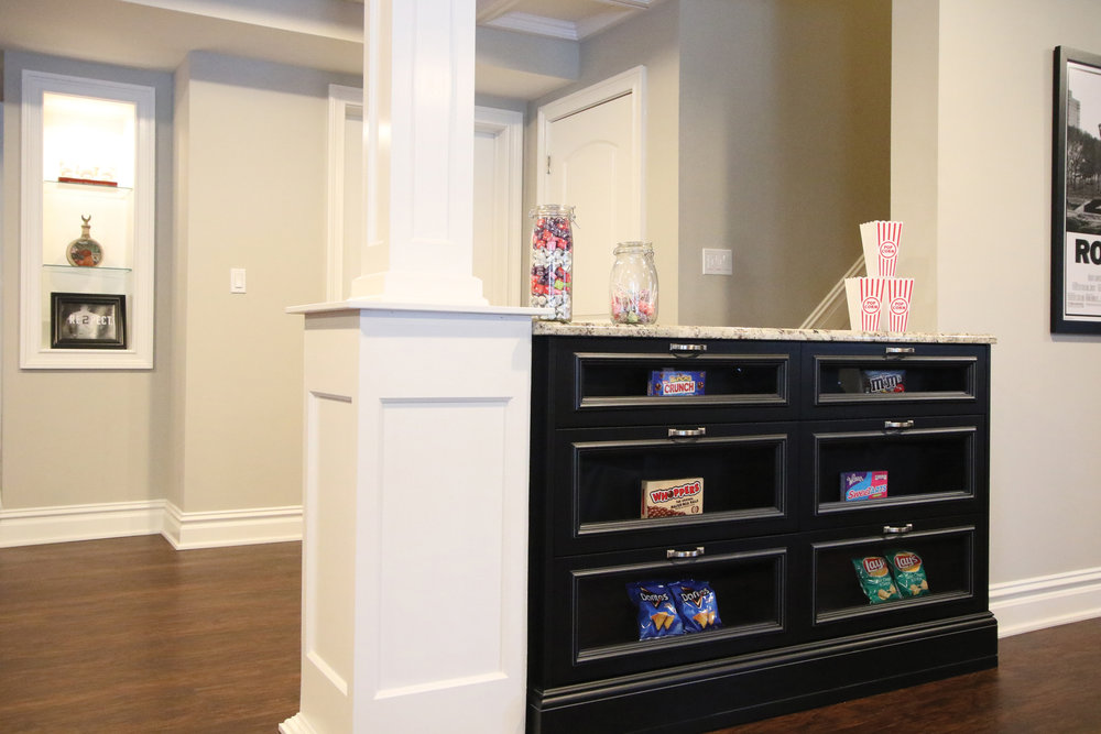 A personal-preference candy counter becomes the wall divider for the media room