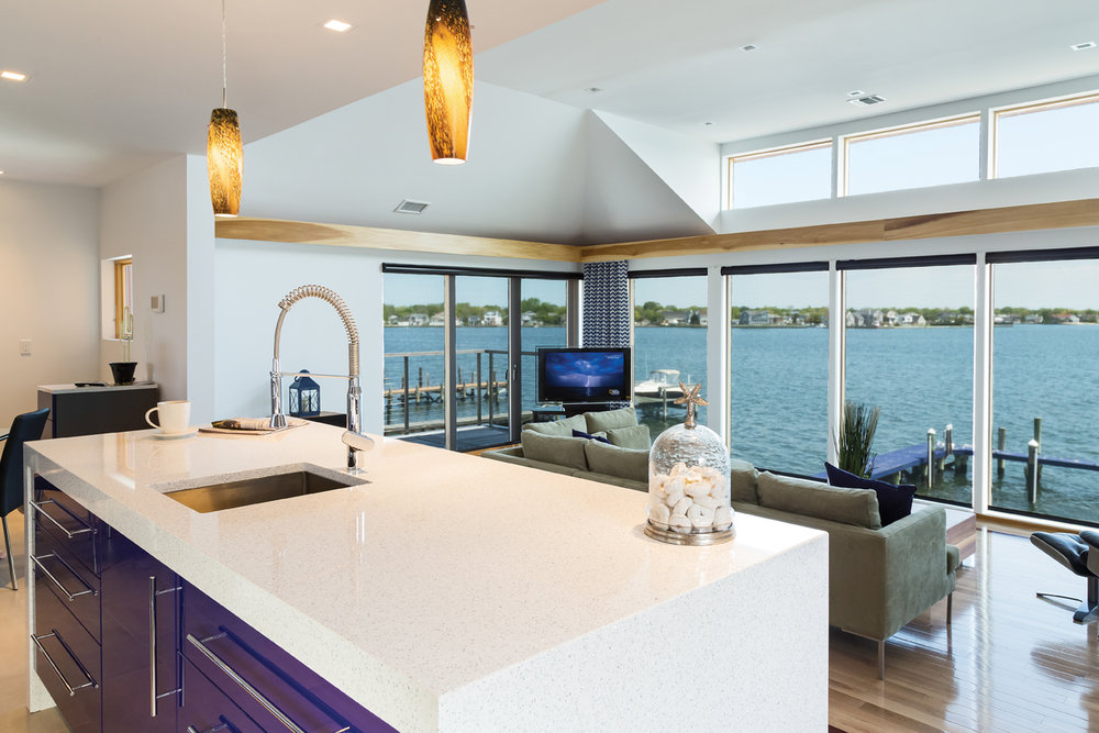 "The kitchen and sunken living room overlook South Oyster Bay. The sleek lines and Cambria ""Whitney"" Quartz countertop compliment the magnificent views."