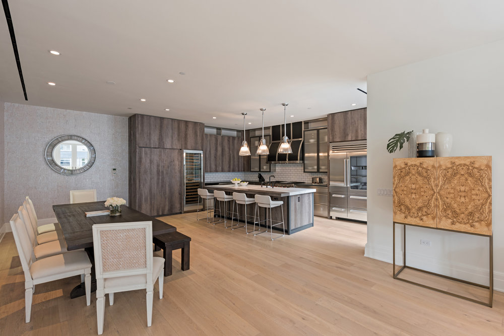 You always want a kitchen with the capacity to entertain. Here there are a variety of different seating options for all who enter, with an open path of conversation whether one is cooking or enjoying the food. Different elements of wood from cabinetry, to table and the accessory storage accentuate the bright hardwood flooring – producing a comfortable, appetizing tone in a modern space