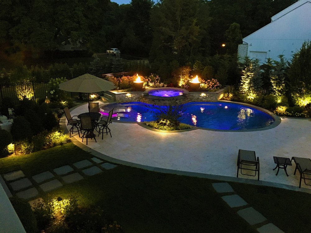 A free form shaped pool was designed with a curved pool terrace that works off the shape of the pool. Bluestone paths with lawn joints soften the hardscape.