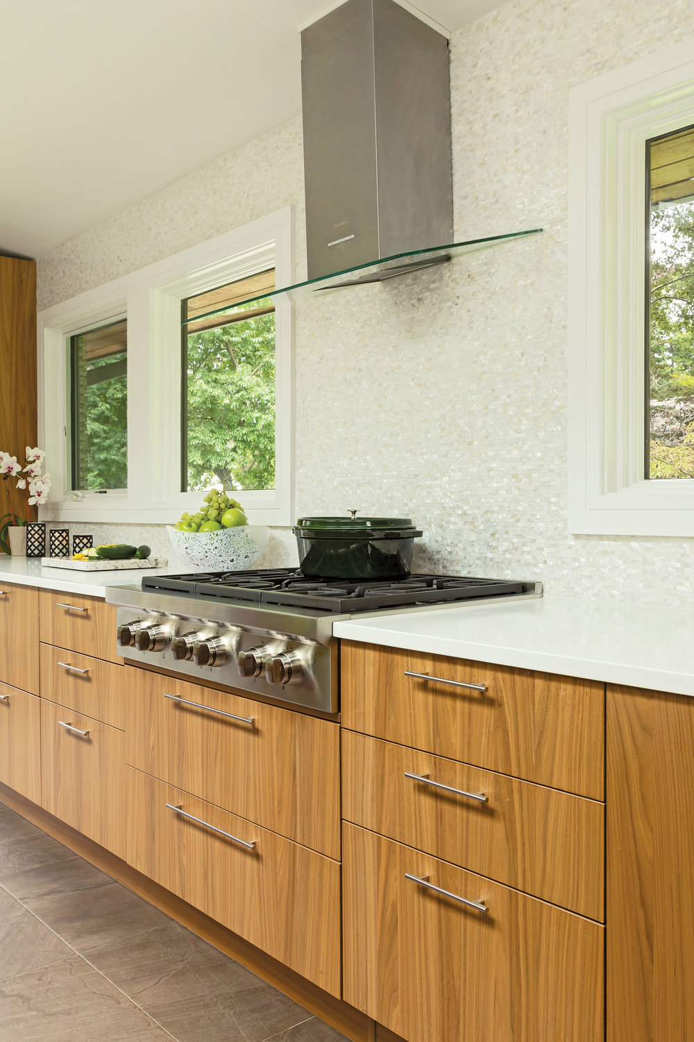 Wolf range and hood became the axis of the room in this one-of-a-kind kitchen with custom, book-matched vertical grain walnut cabinets imported from Italy.  Mother of pearl backsplash creates spa like feel.