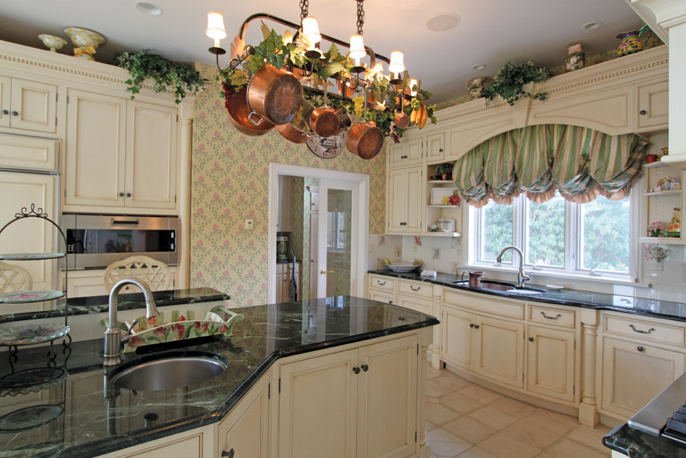 This light and cheerful kitchen was where the design process began. The cabinets are a soft glazed cream color, with dark green marble on the counters.