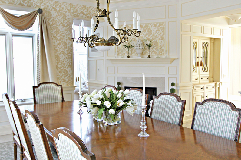 Bright and cheery, the dining room has a very inviting feeling for a lovely family dinner and highlights a beautiful fireplace.