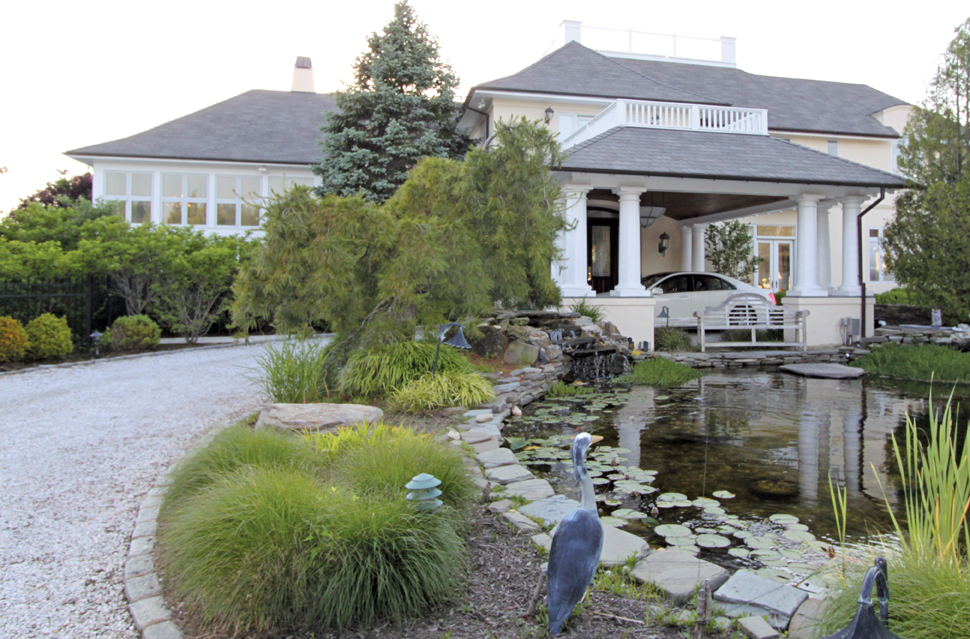 The approach to the front of the home is architecturally beautiful with pillars and widows walks. The client also installed a koi pond and waterfall, creating a fabulous point of interest.