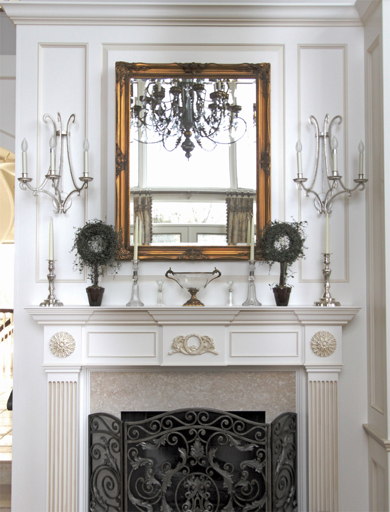 A gilded mirror, crystal and silver candlesticks and topiaries adorn the fireplace mantle.