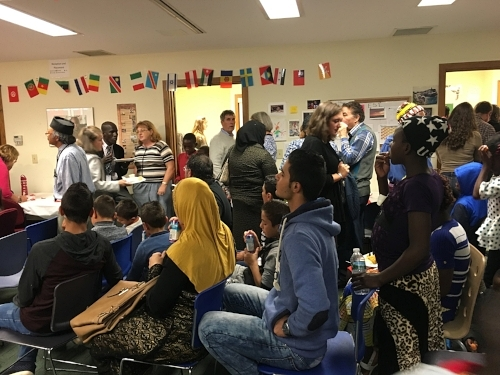 Refugees from a local resettlement agency and folks from my church share food and listen to music together at a potluck. Your presence, even with a language barrier, can be a great message of welcome.