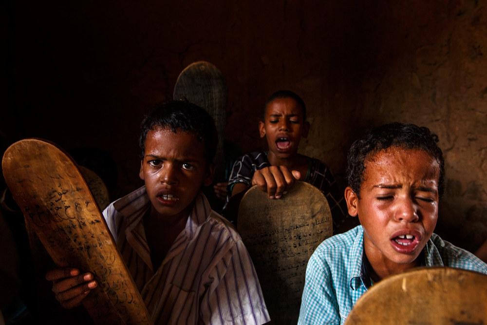 Mauritania,-Adrar---Children-reading-off-of-tablets-and-praying-in-a-Mahadara---traditional-Islamic-school.jpg