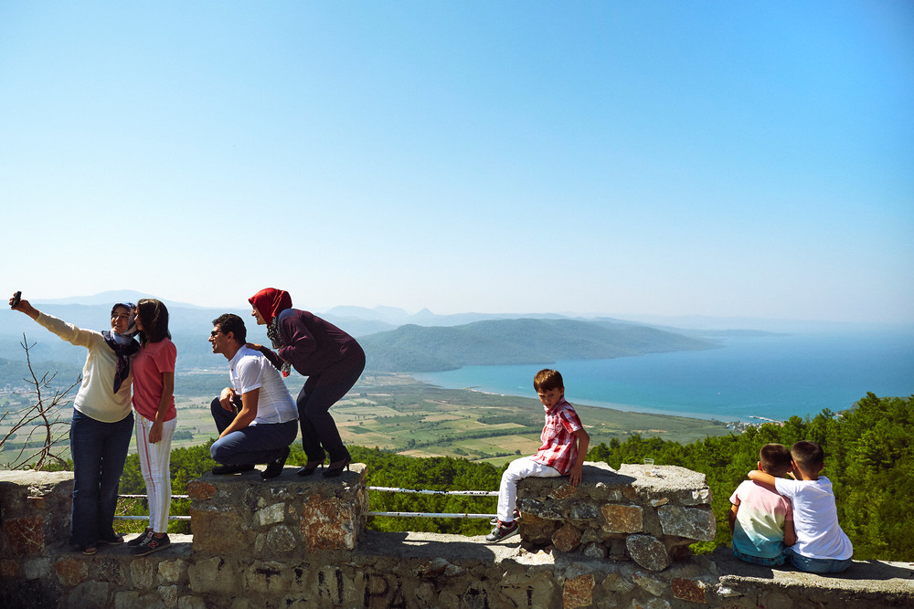 Turkish tourists taking photos from a viewpoint above Fethiye
