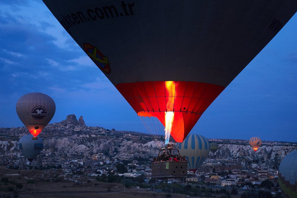 Hot air balloons flying through the Cappadocia landscape