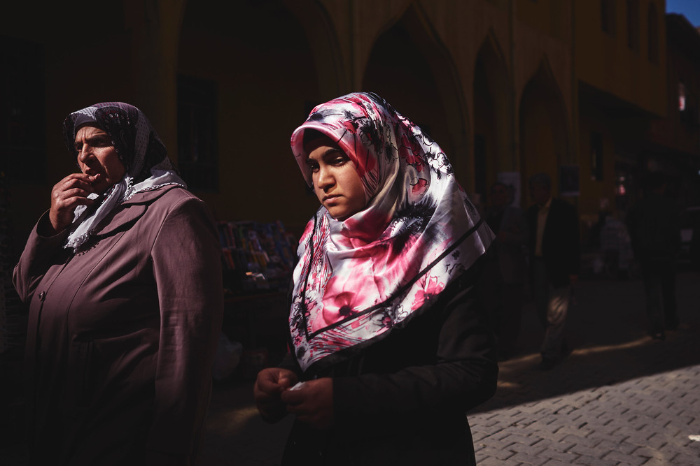Women walk past a Mosque at midday.