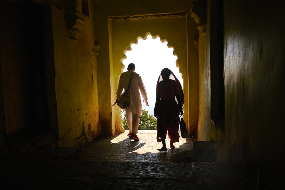 Man and woman walking through an arch.