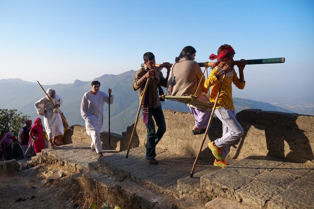 Men carrying a pilgrim up Girnar hill in a dooli
