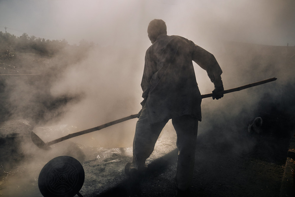 Sugarcane worker near the vat