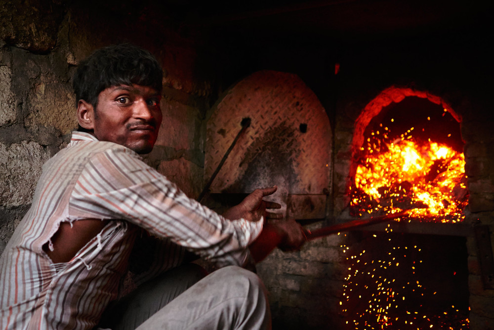 Sugarcane worker putting husks into the oven