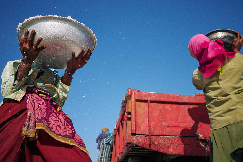 Woman salt worker lifting up a tub of salt