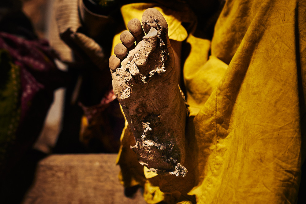 Woman road worker's foot with asphalt stuck to it.