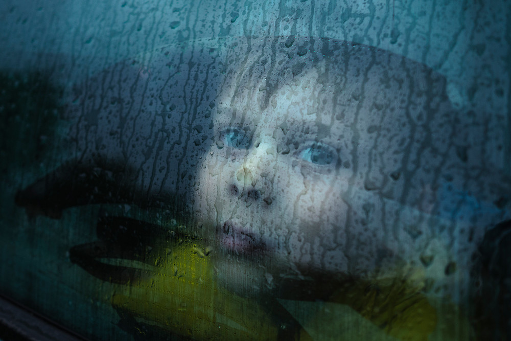 Belarusian boy pressing his head against a car window