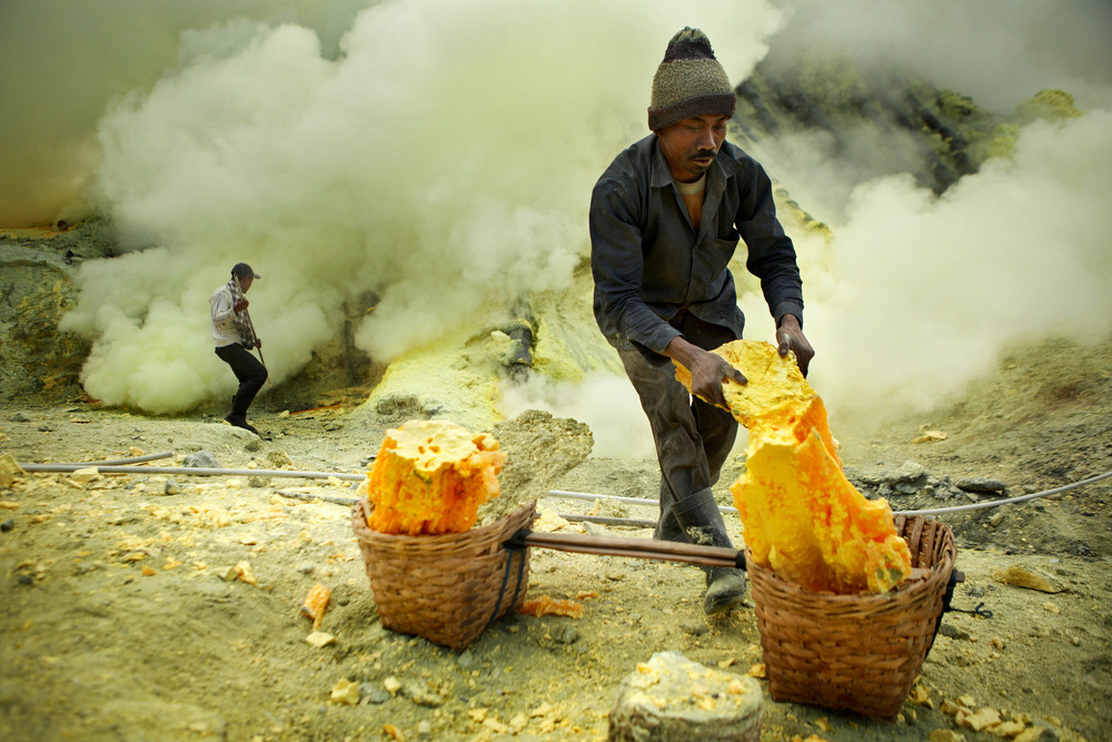 Sulfur miner loads sulfur into his baskets