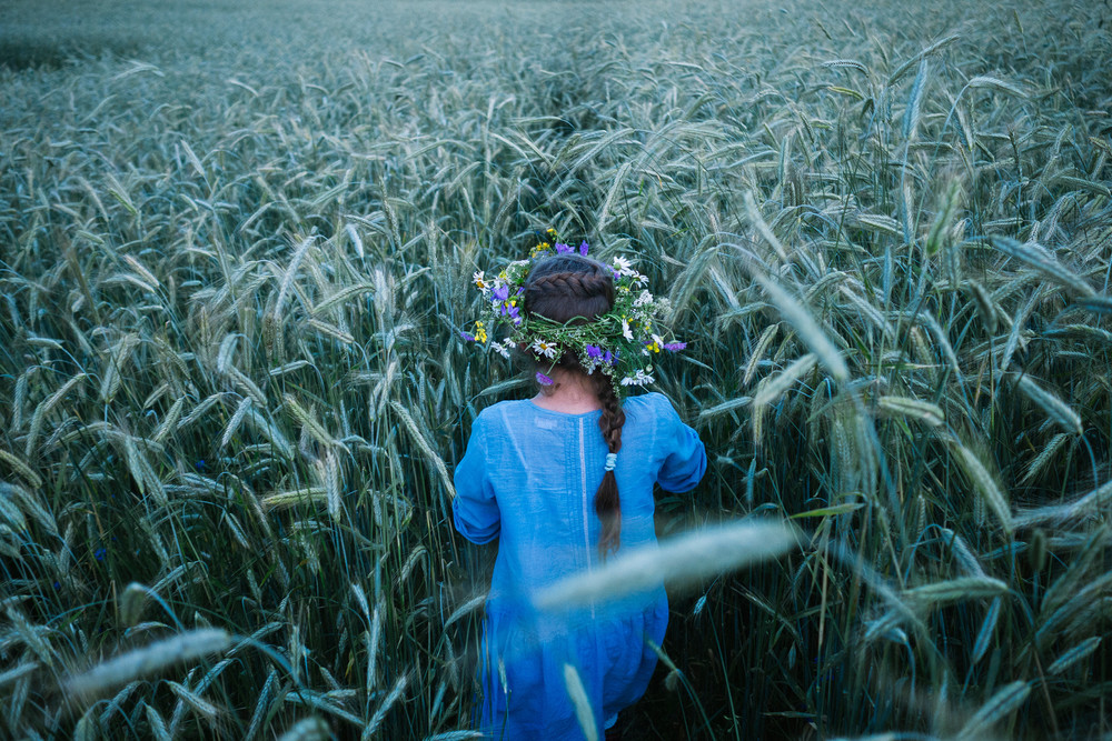 Girl walks through a field of rye in Belarus