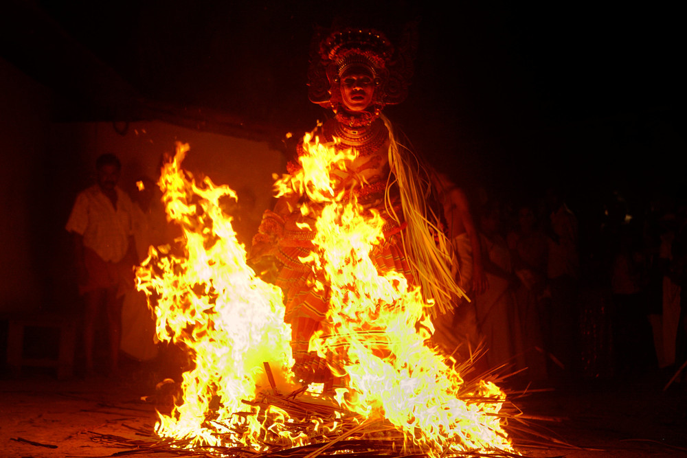 Theyyam performer walking through fire