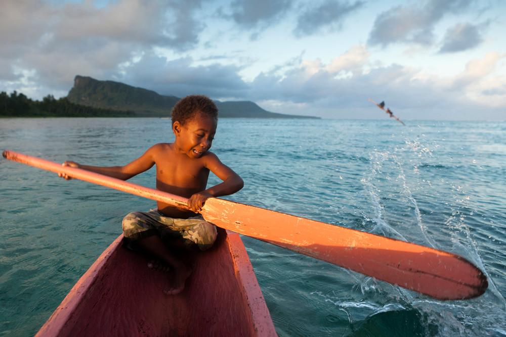 Ni-Vanuatu boy  in a boat in a lagoon