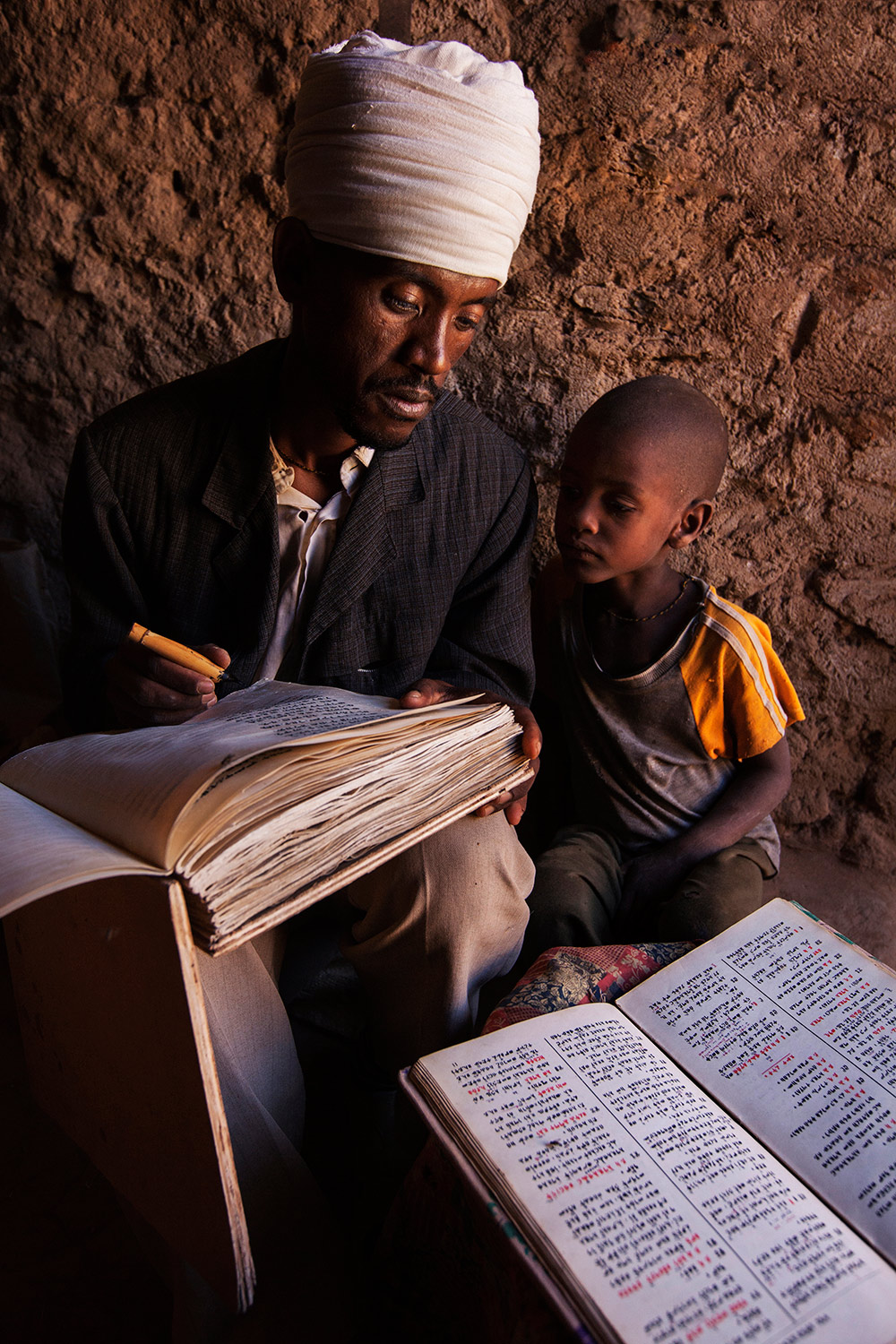 Ethiopian priest teaching his son to write