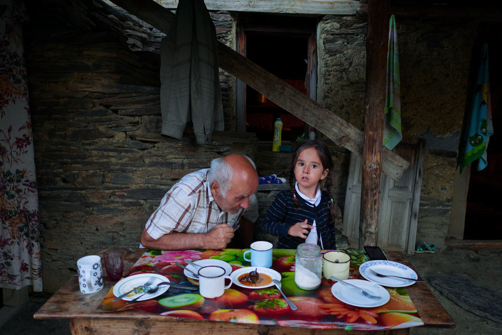 Tusheti-Georgia-Man-and-granddaughter-behind-table