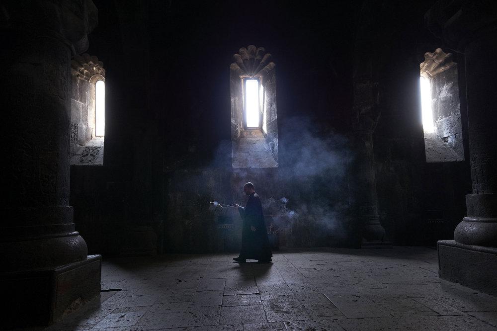 Geghard-priest-blessing-the-inside-of-a-church.jpeg