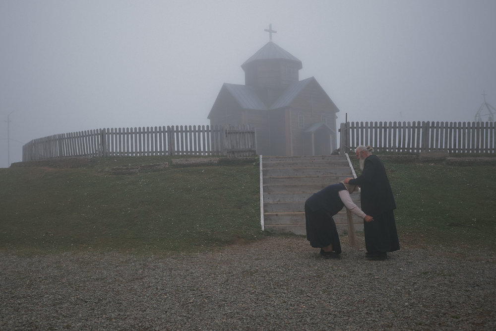 Priest blessing a woman in front of church in the fog Bakhmaro