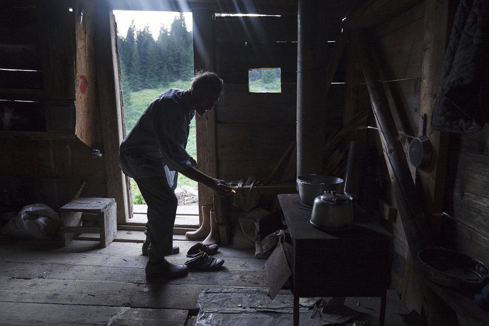 Tamaz forest shepherd lighting the stove in his hut high Adjaria.JPG