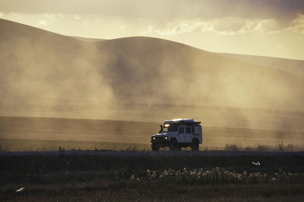 Landrover Defender in the dust at sunset.JPG