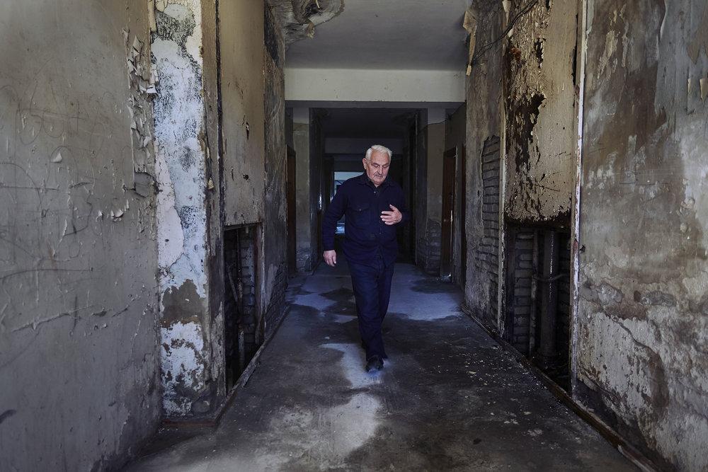 Vakhtang Abkhazi refugee walks through the corridor of an abandoned sanatorium