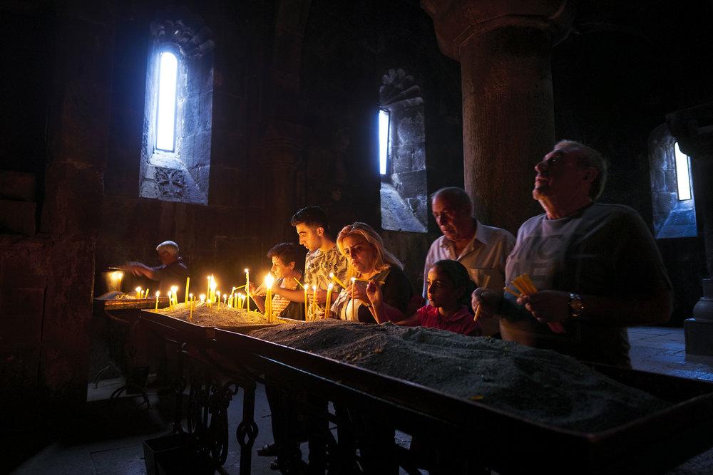 Devotees putting up candles at Geghard church, Armenia.JPG