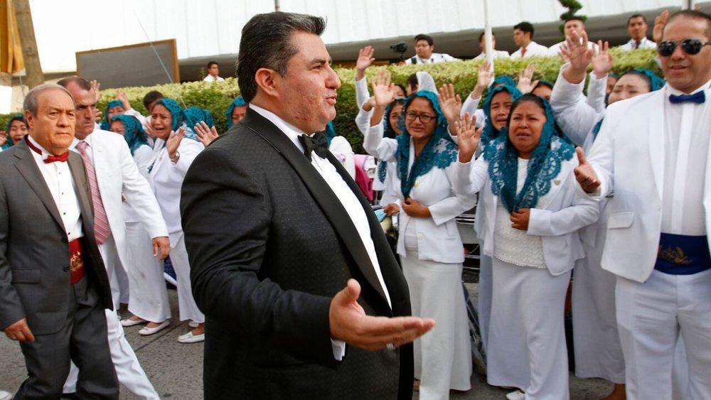 """Aug. 14, 2018 photo, Joaquín García, 50, greets members of his church """"La Luz del Mundo"""" in Guadalajara, Mexico"""