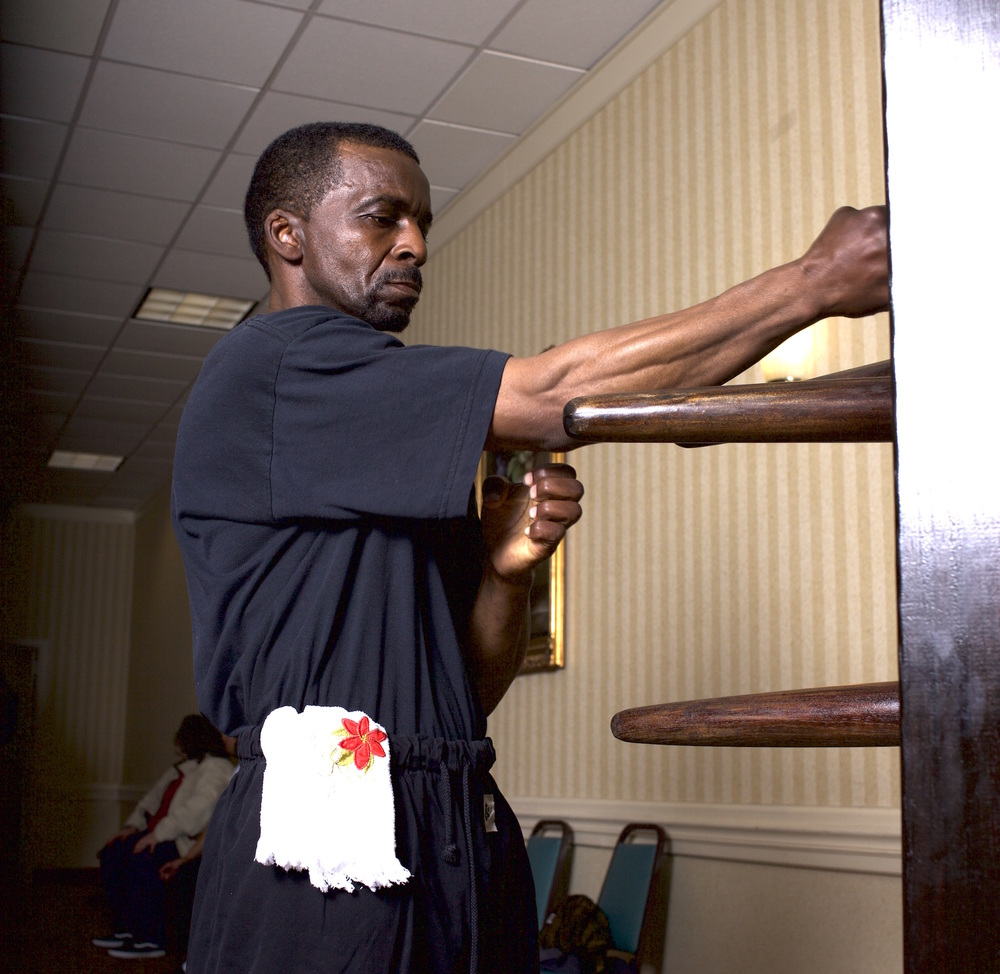 Moy Tung Kung Fu training includes the 108 Muk Yan Jong (Wooden Dummy) form. Senior Master Instructor Charles Moseley practices Chung Choi (center punch) on the Jong.
