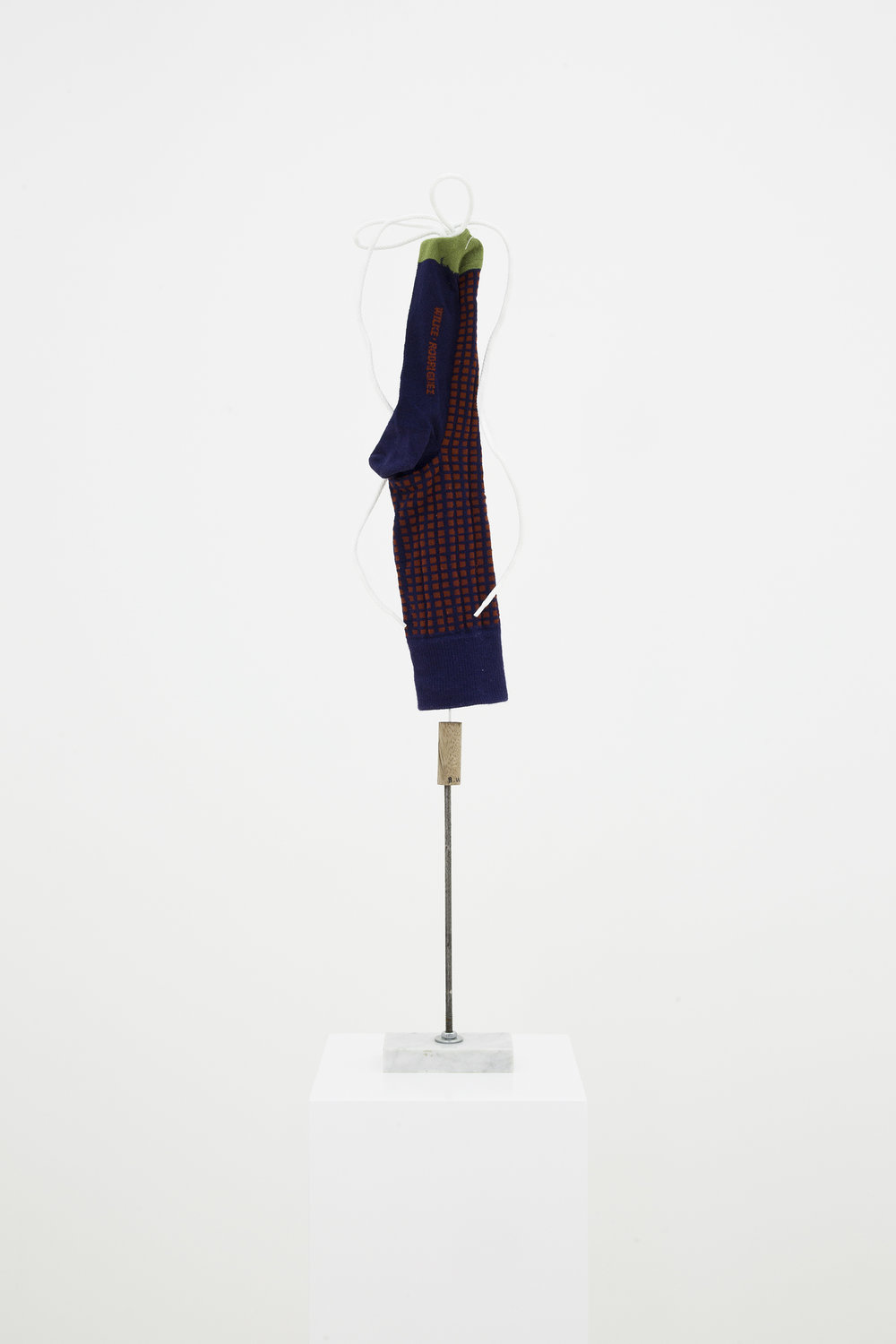 Untitled (Blue with red checkers sock), 2016. Cotton sock, shoelace, marble, wire, metal, wood, and thread, 69 x 10 x 5.25 cm (27 x 4 x 2 in)