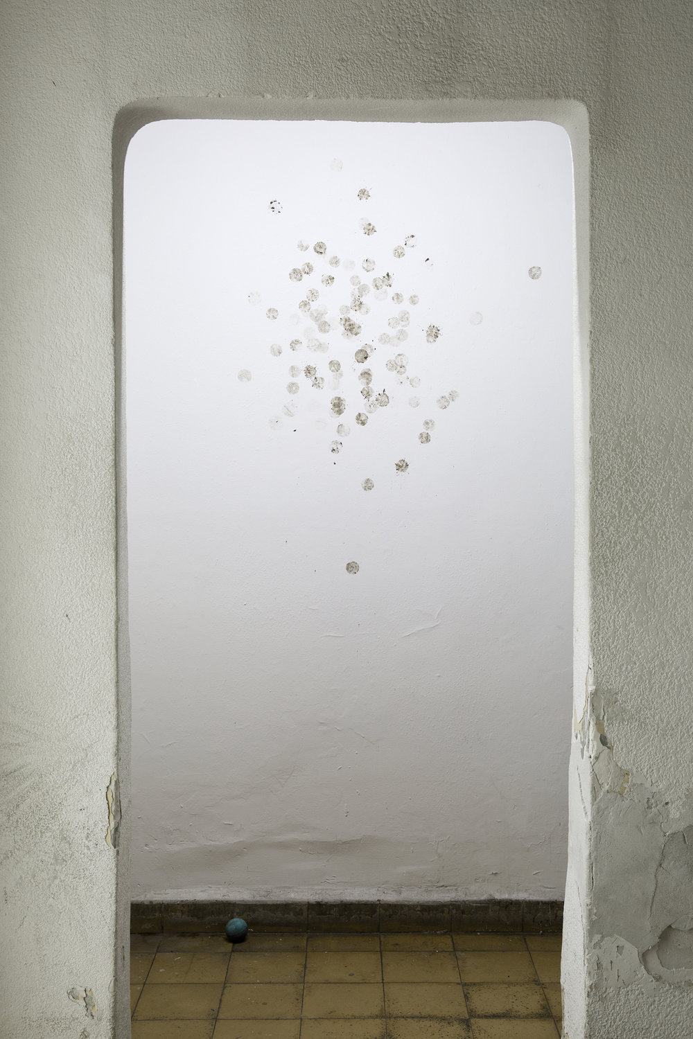 Ball, 2017. Installation with muddy ball against wall (Unique), dimensions variable.