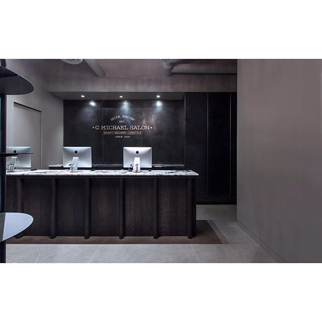 The receptionist area of our interior design for @gmichaelsalon features a massive ebonized white oak desk with granite top that we designed. A wall of cabinets are cladded in blackened steel with integrated formed steel handles.