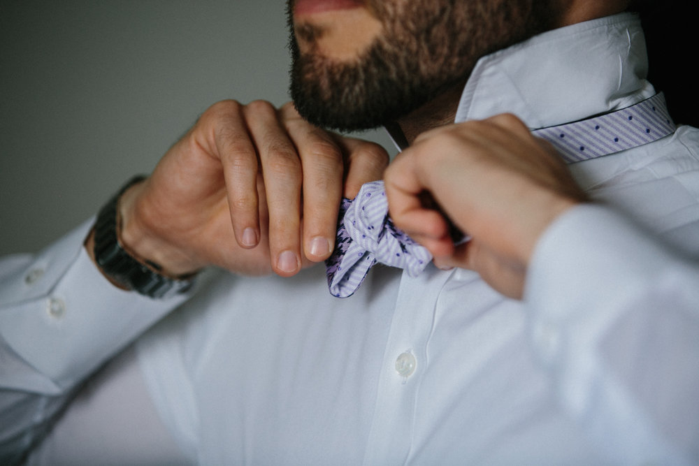 Groom tying bowtie