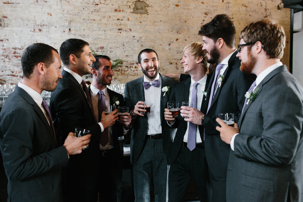 Groomsmen and groom toasting